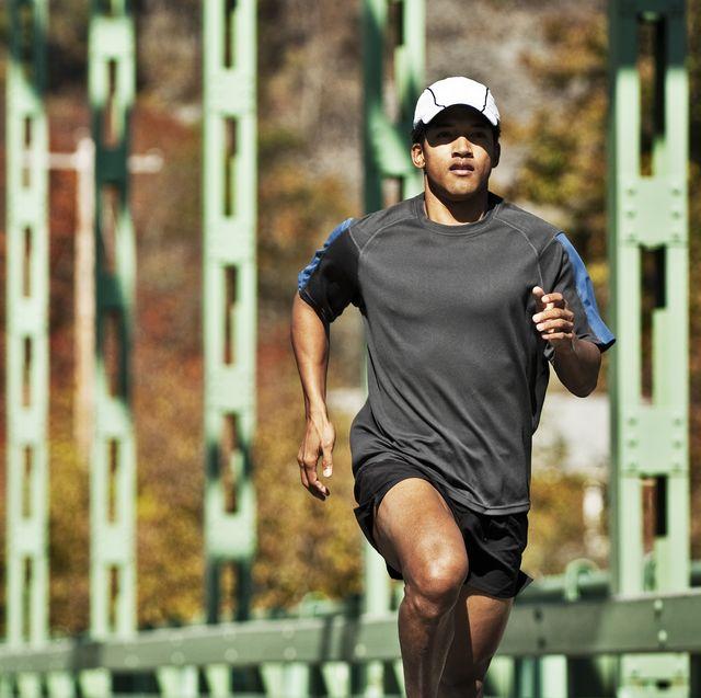 man running across green bridge