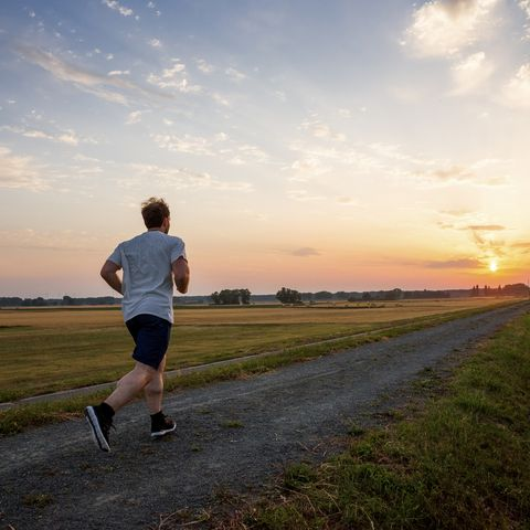 man running in rural landscape at sunset