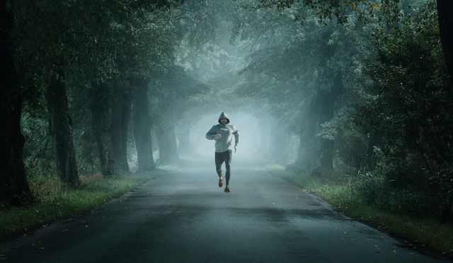 man running on the foggy morning