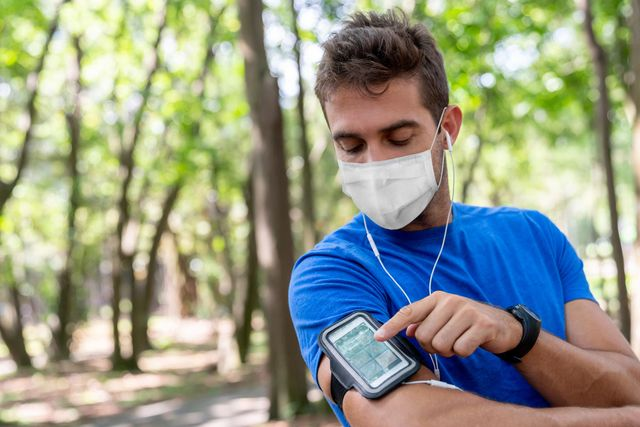 man running outdoors wearing a facemask and using an arm band for his cell phone