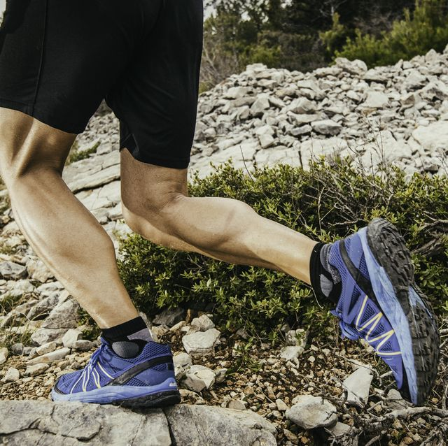 man running up a rocky hill