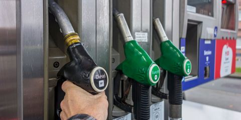 man selecting diesel fuel pump nozzle at gas station for refueling his car in europe
