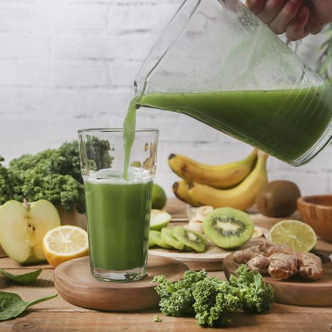Man serving glass of green smoothie surrounded by ingredients
