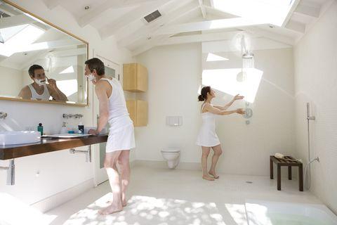 Man shaving and woman testing shower in bathroom.