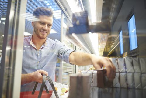 Man shopping for groceries in supermarket freezer
