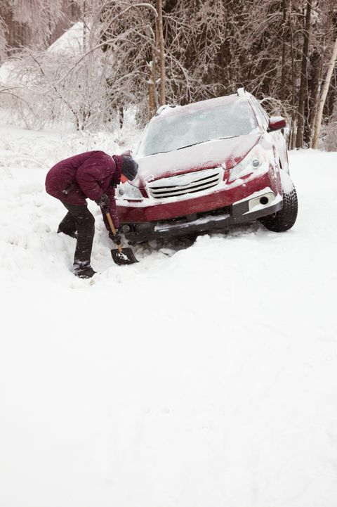 Man shoveling snow to rescue car from ditch