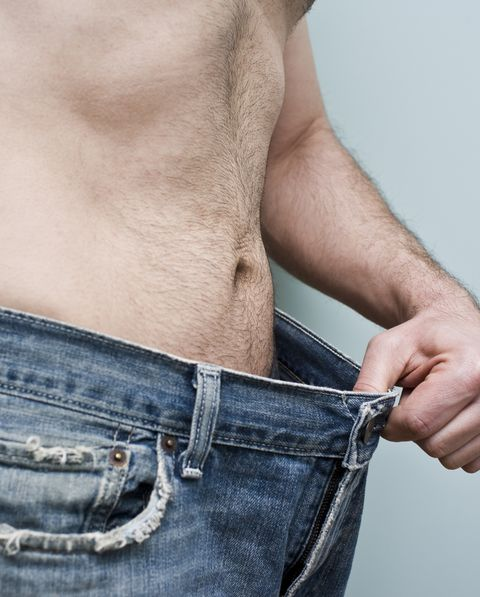 Man showing weight loss by showing his loose pants