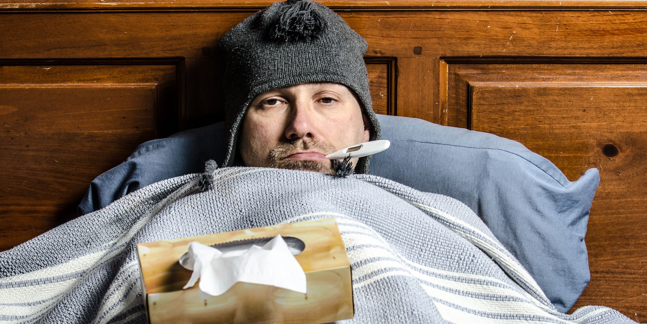 man sick in bed with a thermometer in his mouth