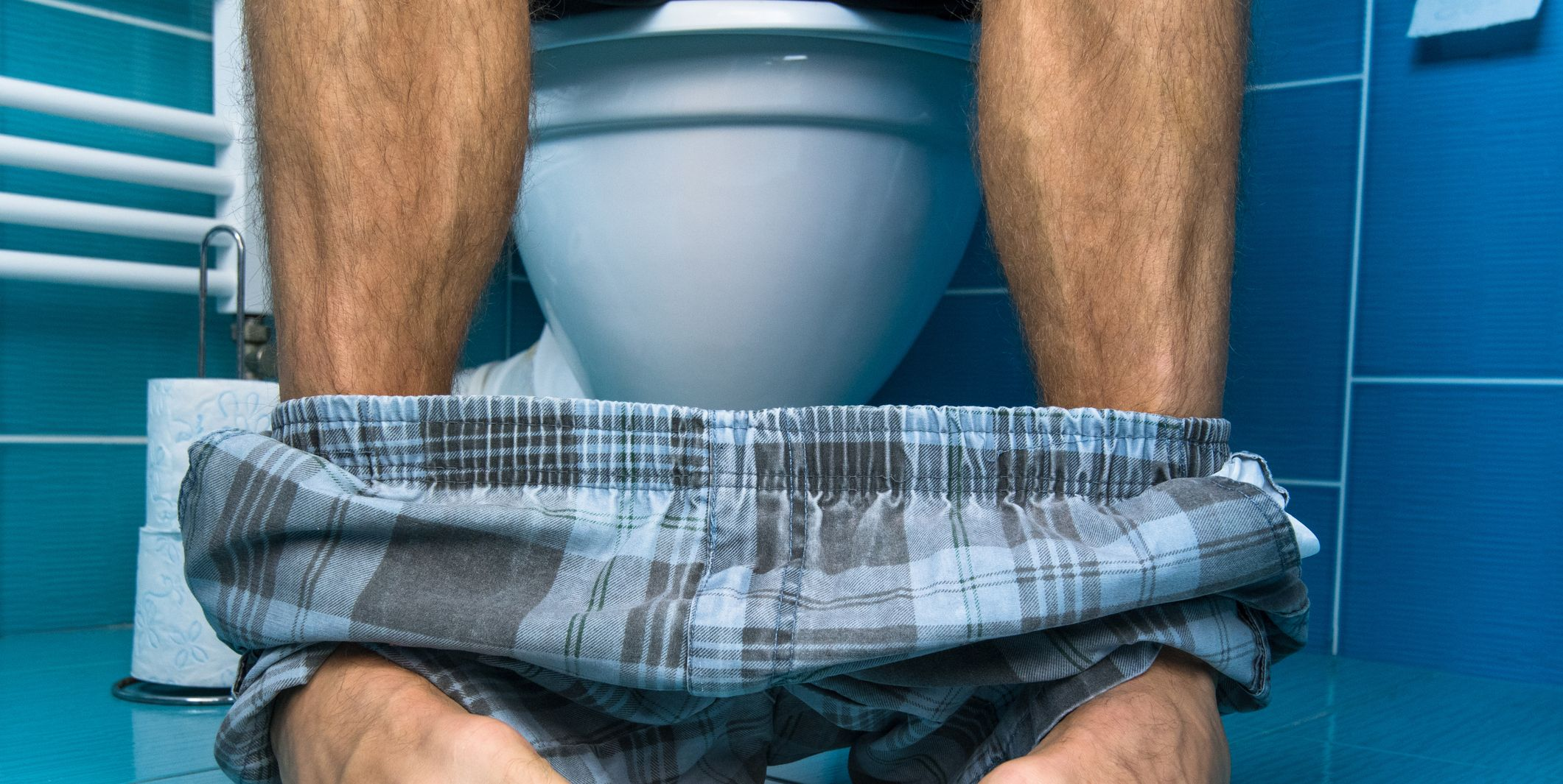 A man sit on the toilet.