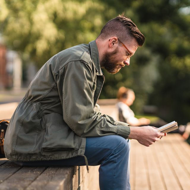 man sitting in a park reading a book