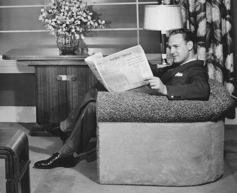 Man sitting in armchair, reading newspaper (B&W)