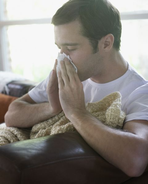 Man sitting in living room blowing nose