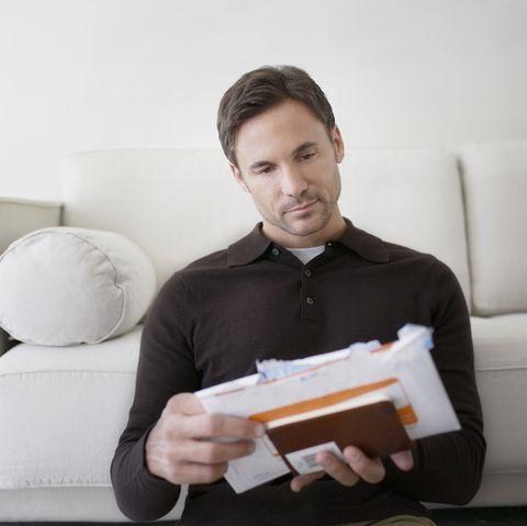 Man sorting bills at home