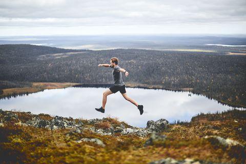 Man sprinting on rocky cliff top, Keimiotunturi, Lapland, Finland