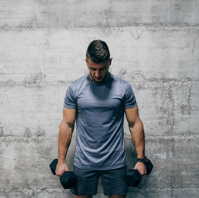 Man standing and holding dumbbells while looking down. Pain is temporary, quitting lasts forever.