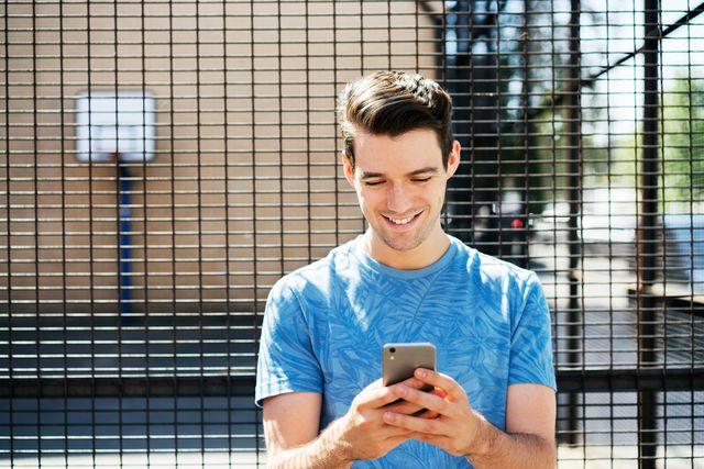 man stood using smart phone