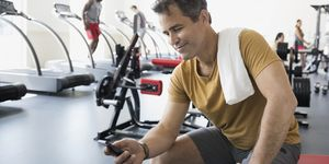 Man texting with cell phone at gym