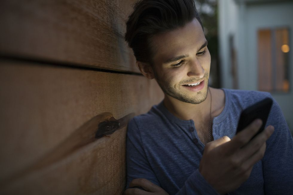 Man texting with cell phone on dark patio