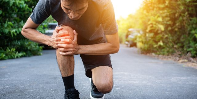 man touching knee in pain on road
