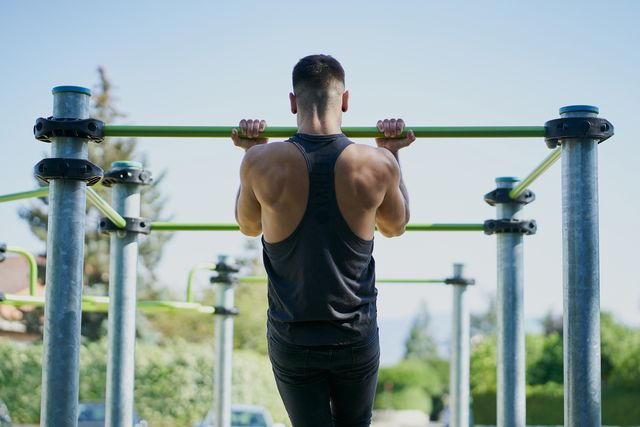back view of a man practicing calisthenics in a park on sunny day