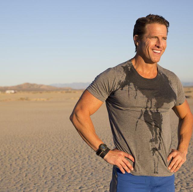 man training, sweating and taking a break on dry lake bed, el mirage, california, usa