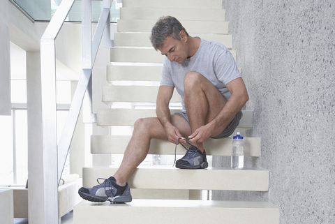 Man Tying His Shoes on Stairway