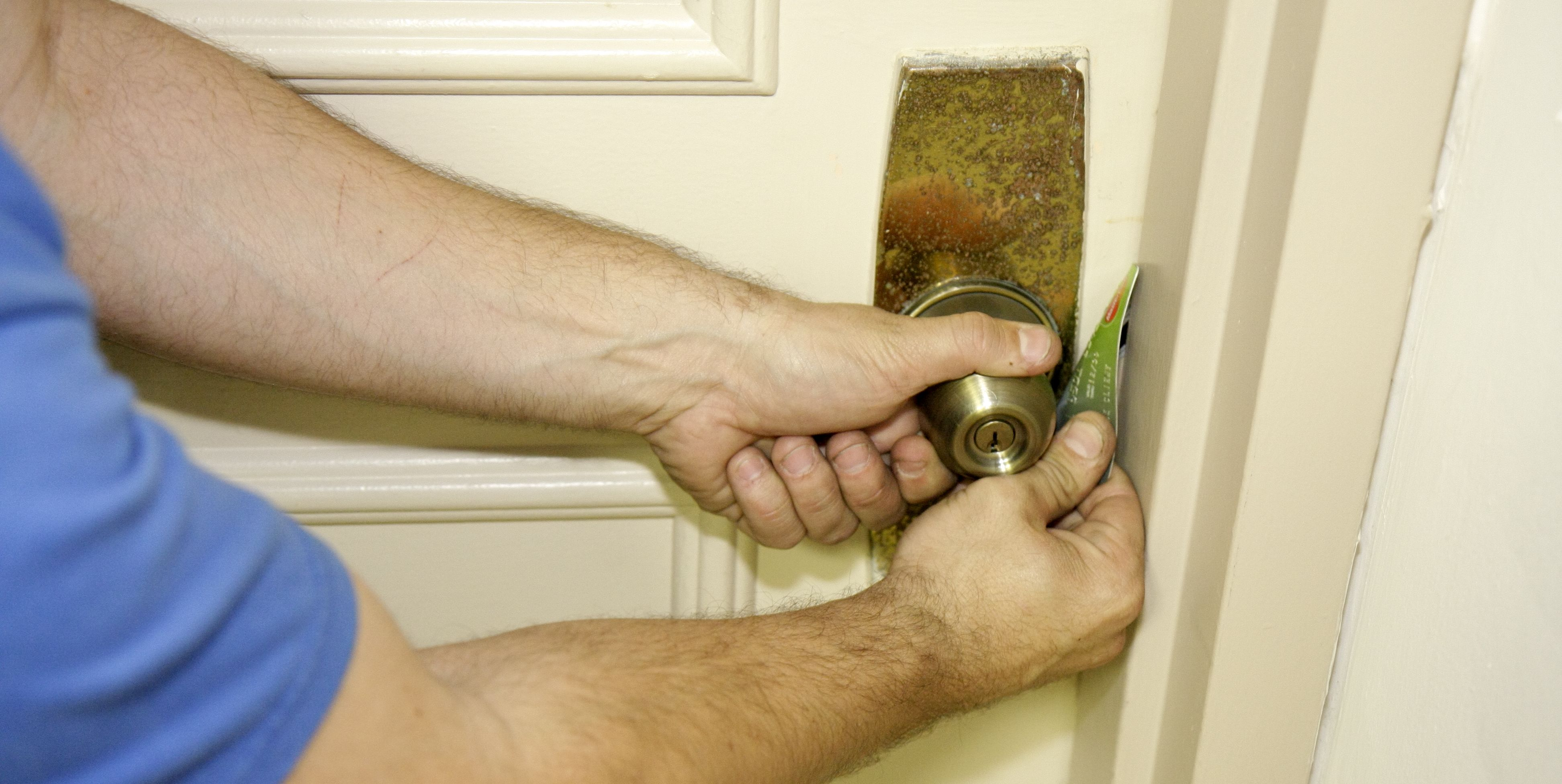 A man using a credit card to open a door.