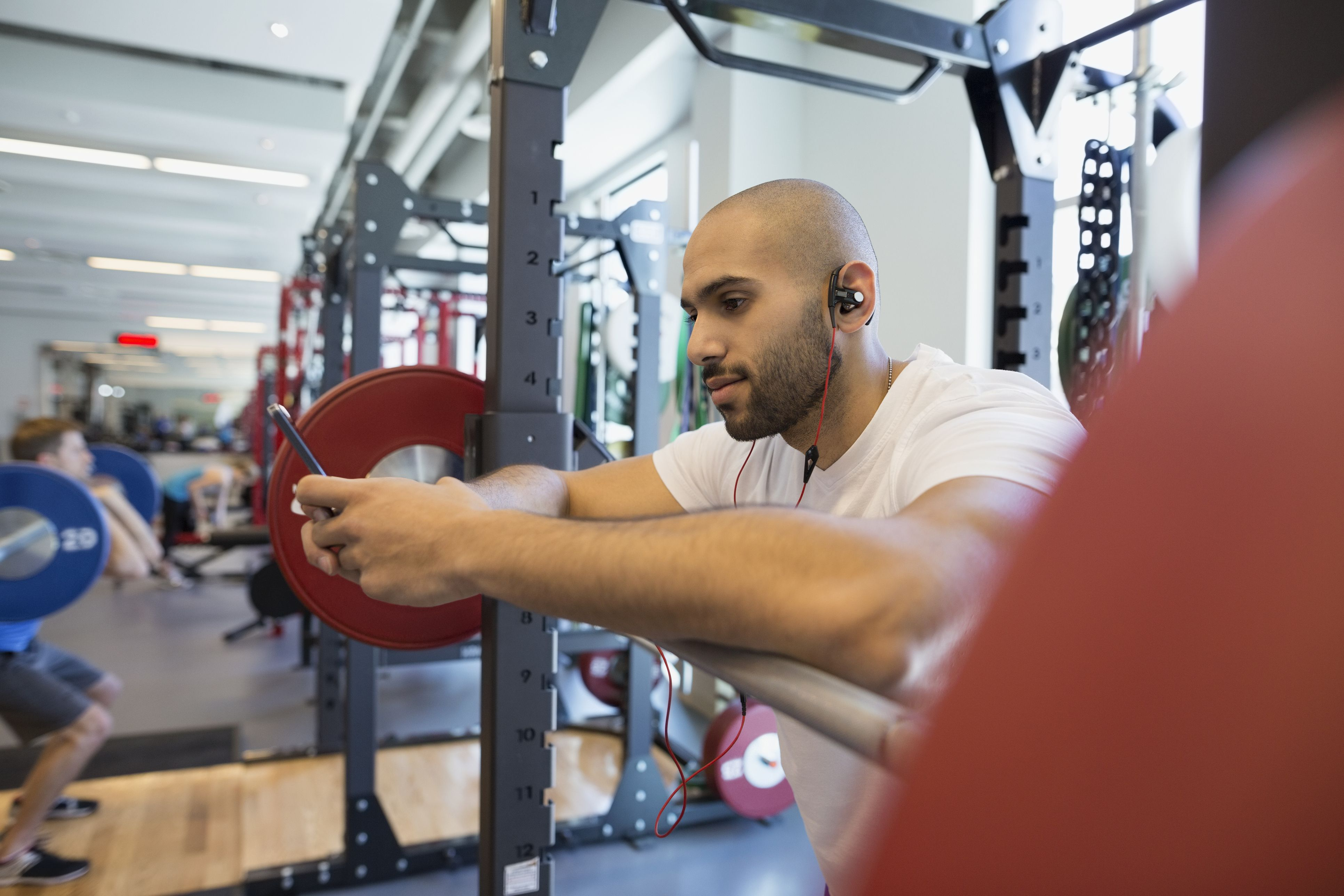 Man using cell phone at barbell in gym