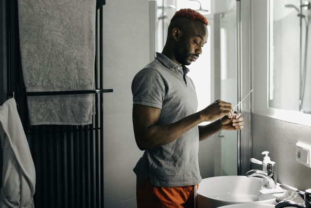 man using corona virus test swab in his bathroom