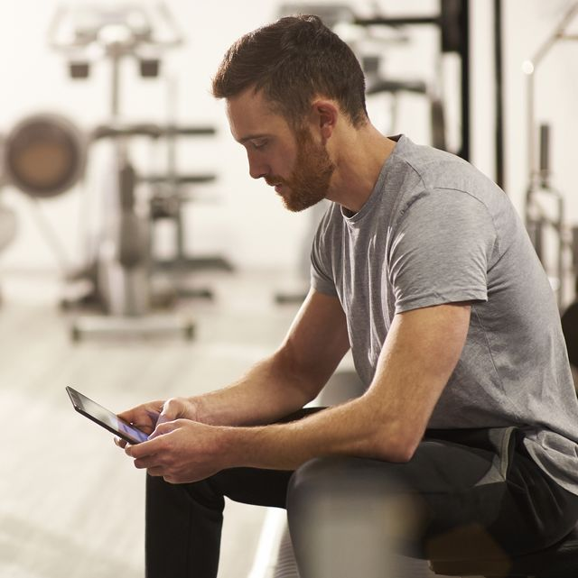 Man using digital tablet in gym after exercising.