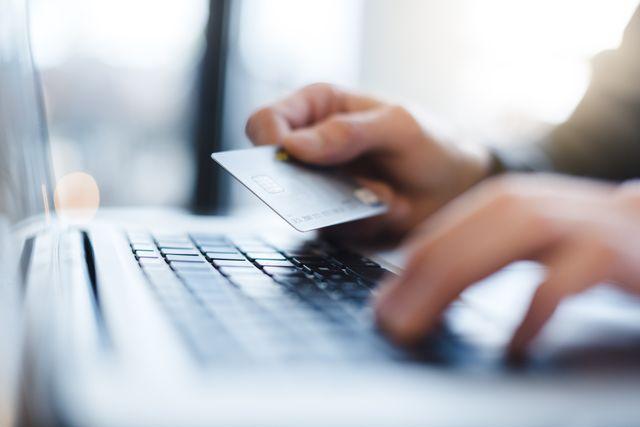 man using laptop and holding credit card closeup