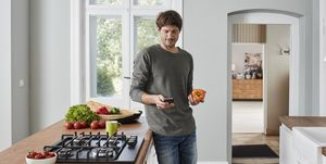 Man using smartphone and holding bell pepper in kitchen