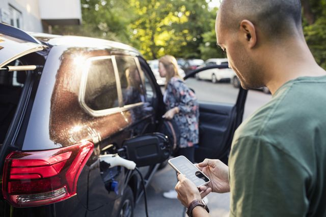 man using smartphone with woman standing by car in background
