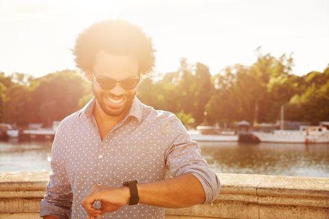 Man using smartwatch next to river.