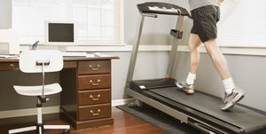 Man using treadmill by desk, rear view