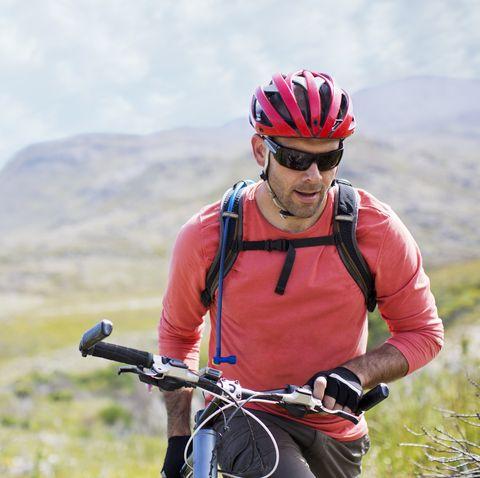 Man walking bicycle in rural landscape