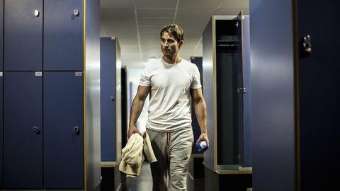 Man walking in locker room of health club