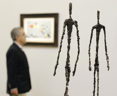 A man walks past a sculpture entitled 'T