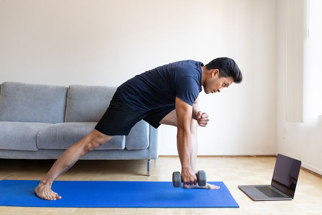 man watching online video and doing dumbbell exercises at home