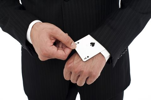 man wearing a suit pulling an ace of spades out of his sleeve