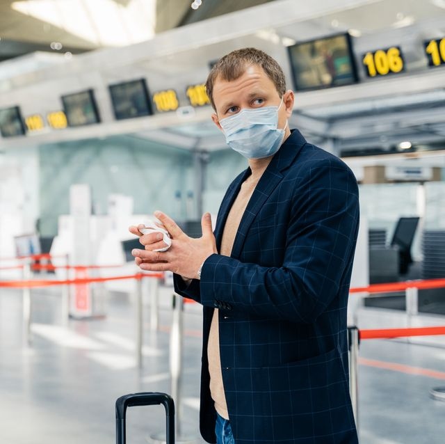 man wearing mask cleaning hands at airport