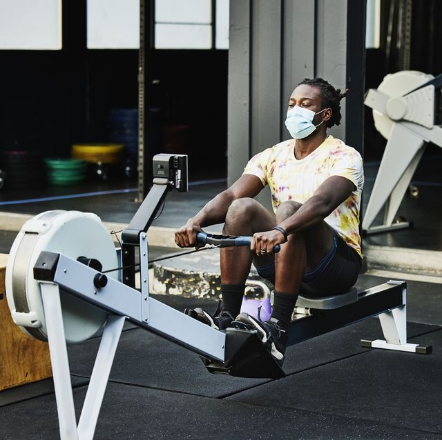 man wearing protective face mask working out on rowing machine at outdoor gym