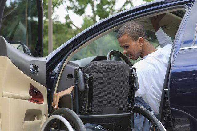 man who had spinal meningitis entering his car with his wheelchair