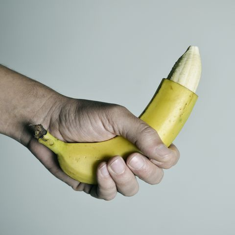 man with a banana with the tip of its skin removed