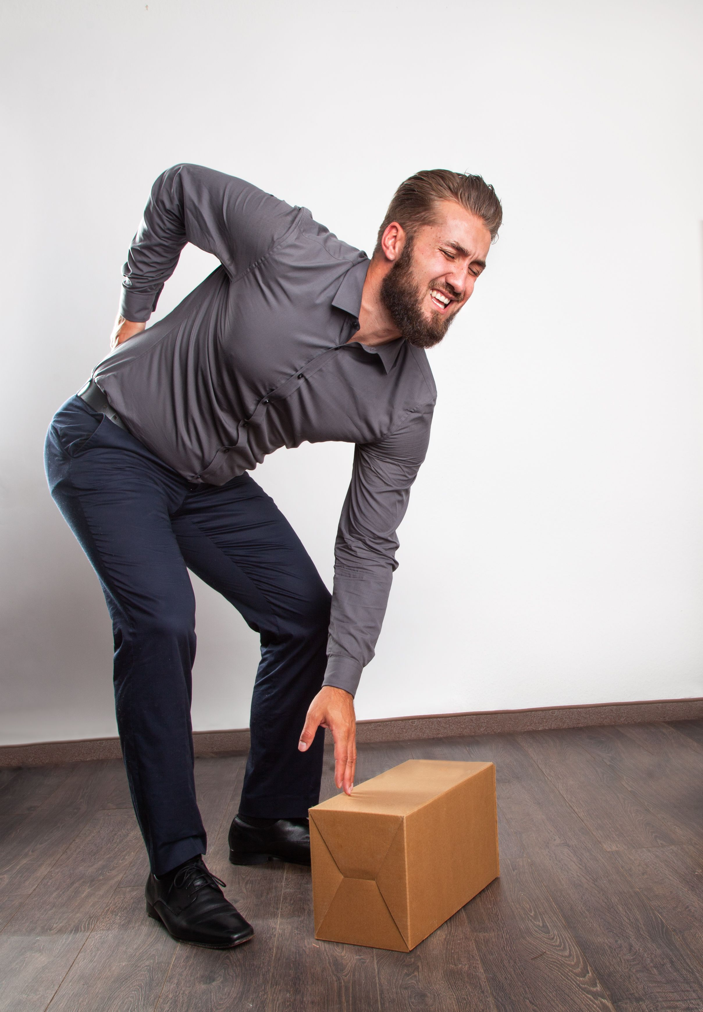Man With Backache Reaching Box While Bending Against White Wall