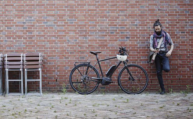 un hombre con una bici eléctrica aparcada