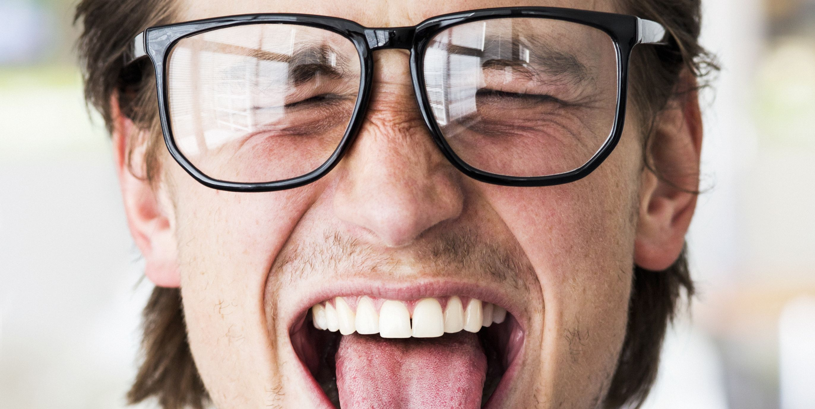 Man with glasses with his tongue out