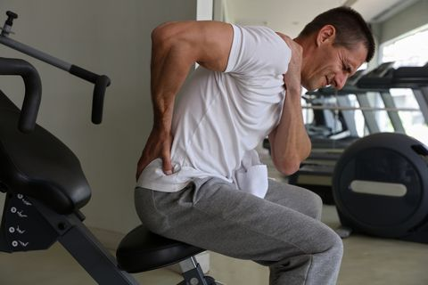 Man with low back pain in gym. Sports exercising injury