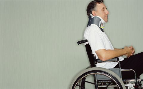 man with neck brace in wheel chair in hospital