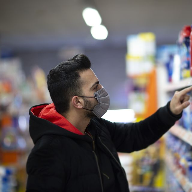 man with the mask on his face at the supermarket is looking for a disinfectant